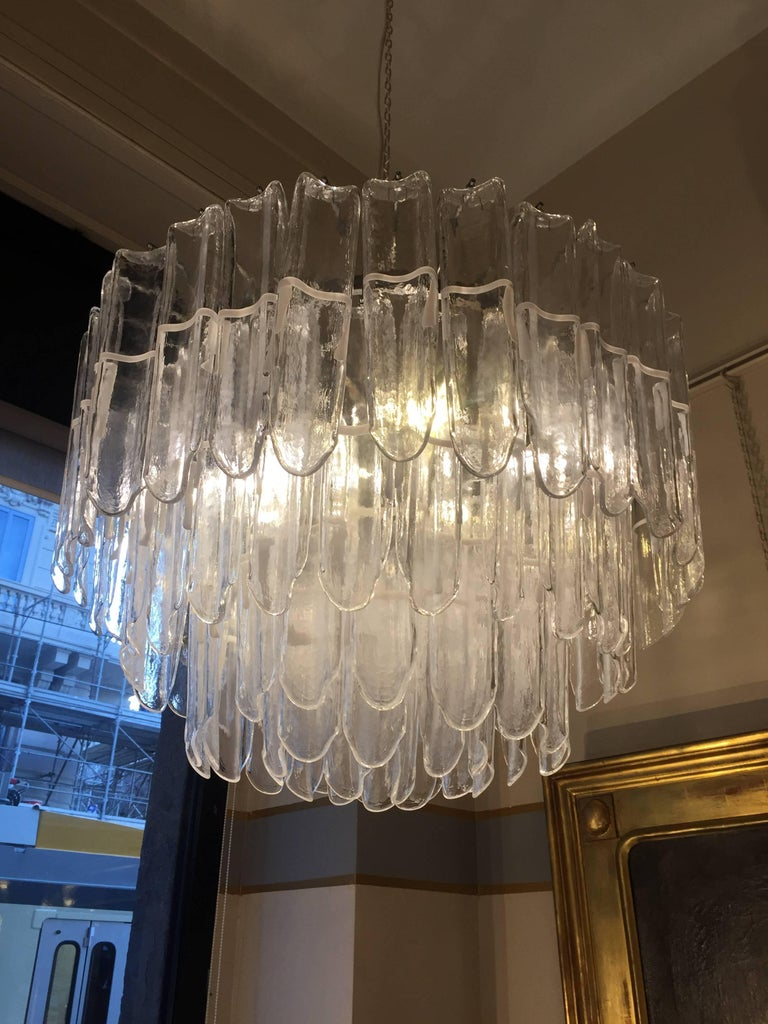Italian art glass chandeliers attributed to Mazzega, circa 1970   Rare pair of three layers Murano glass chandeliers most probably produced by Mazzega in 1970s and designed by Vistosi. These chandeliers are composed by squared transparent big