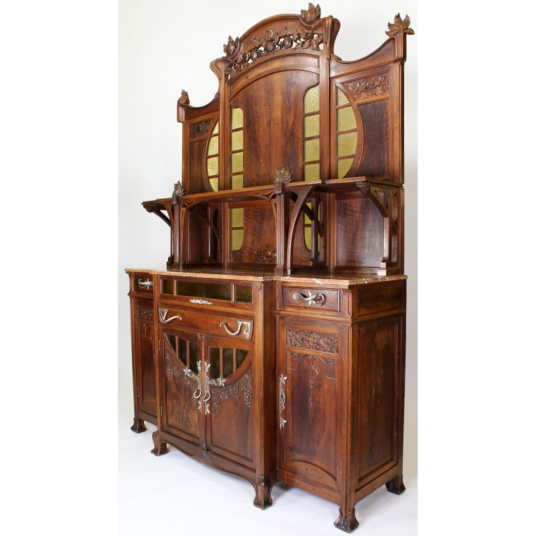 A fine and large Italian 19th-20th century Art Nouveau carved walnut credenza buffet server by Vittorio Valabrega (1861-1952). The tall finely carved walnut body with twin center doors carved with grape vines, fitted with molded yellow-craft-glass