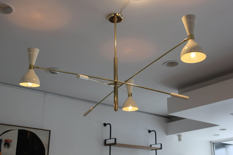 Large-scale three-armed ceiling light in style of Stilnovo with white cone articulating shades and brass arms.