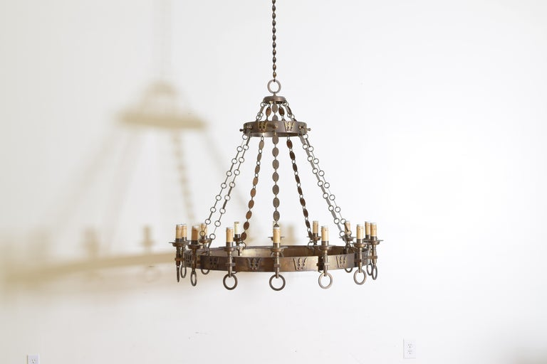 The chandelier having two concentric rings decorated with crowns, with 14 torcheres attached to the outers, the rings connected by oval brass disks.