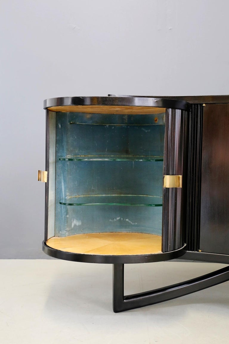 Wonderful furniture in ebonized wood of Italian manufacture of 1940-1950. The cabinet is also suitable as a bar corner because of its drawer hidden in the shelf. Inside the cabinet we find thick glass of Fontana Arte. On the sides of the cabinet