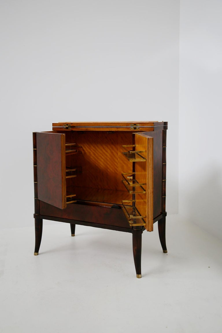 Rare and magnificent bar cabinet designed by Tomaso Buzzi, circa 1930. Verified by the Tomaso Buzzi foundation archive. The cabinet was designed on commission by a private Milanese house. The cabinet has a double hinged door. Inside we find in the