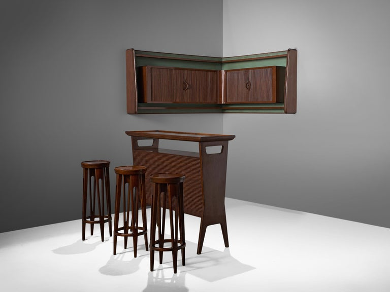 Bar set with stools, bar and wall unit, Italy, 1950s.  This elegant, playful set of bar furniture is made out of Italian walnut and shows typical Italian detailing in the tapered open legs, tambour doors and the diagonal lining. The set consists