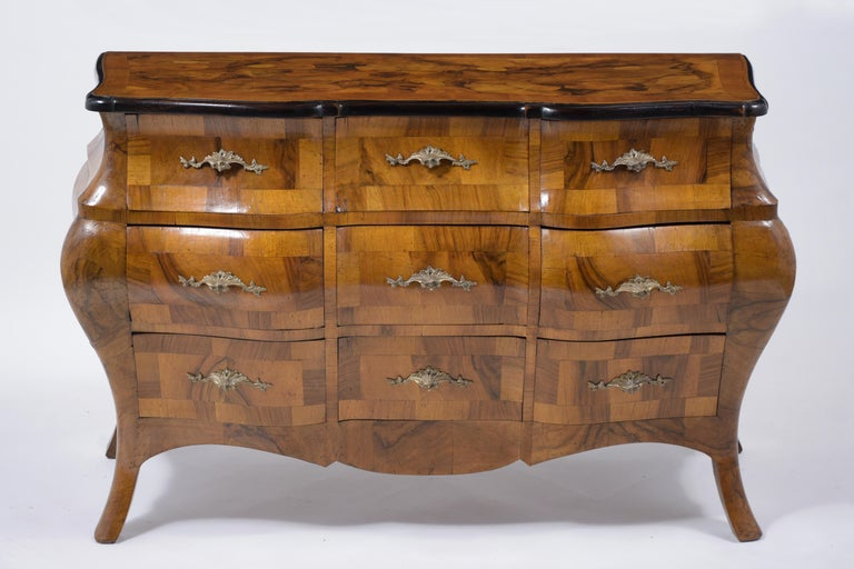 A remarkable early 1900s Italian chest of drawers crafted from solid maple wood covered with burl walnut veneers and a newly waxed patina finish. This eye-catching commode has been professionally restored, features its original finish, beautiful