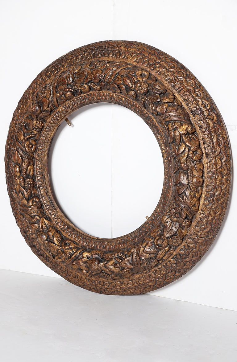 A heavily carved round picture / mirror frame, carved and gilded, rows of geometric and floral carvings, central circle has wheat sheaves embellished with flowers, Italian, late 17th century  Measures: 4.25