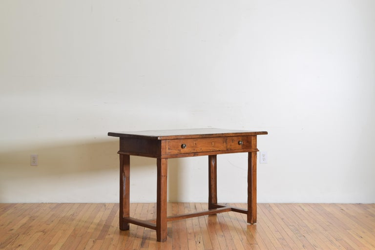 Having a thick solid walnut top overhanging a case with a lower molded edge and housing a single long drawer with two bronze pulls, raised on block legs joined by an H-form stretcher.