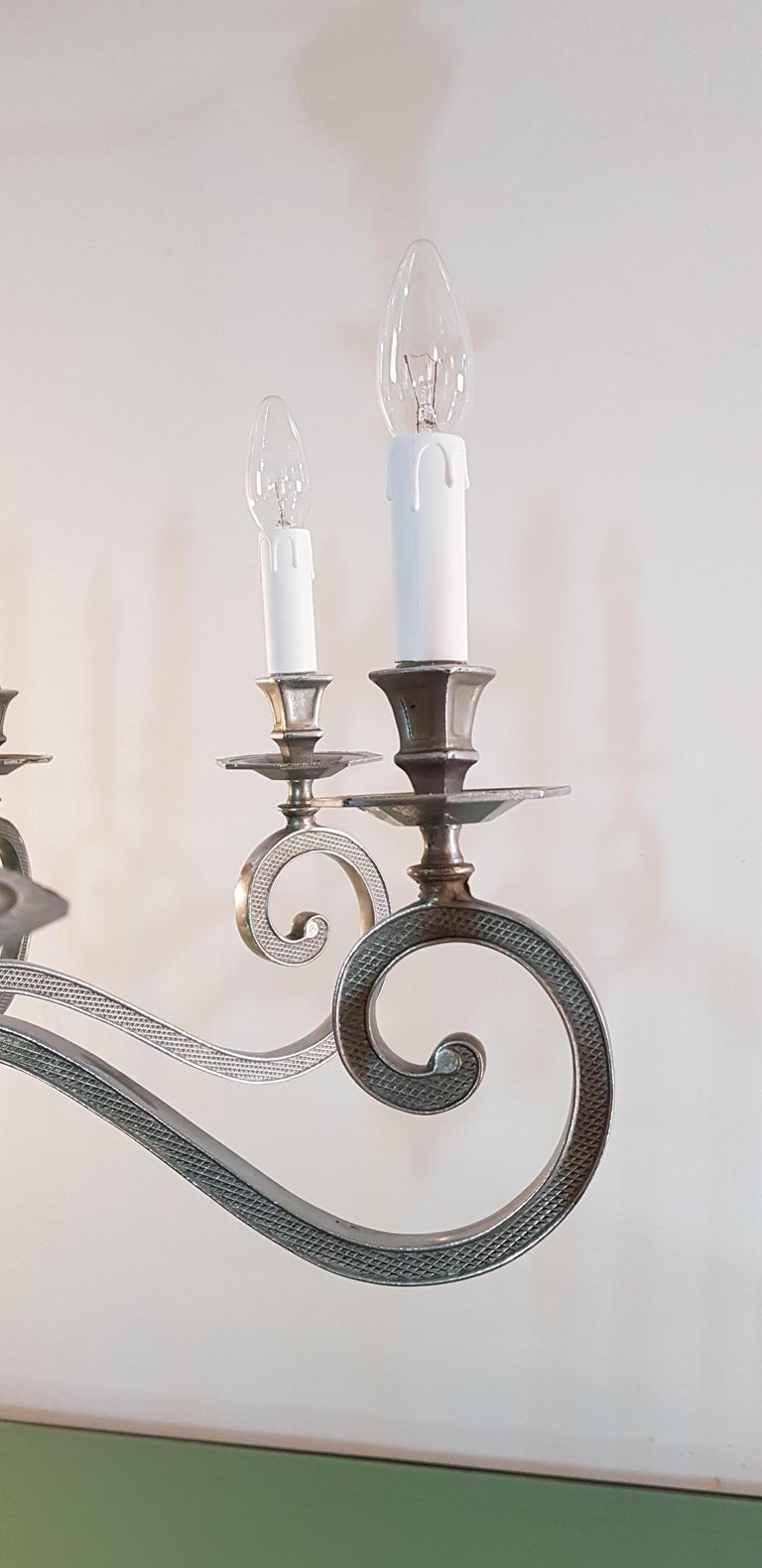 A beautiful and very high quality chandelier in silver metal with eight arms with each holding a candle light. The lamp can be used either as shown in the pictures or with small lampshades. Height without chain is ca 70 cm and with chain ca 110.