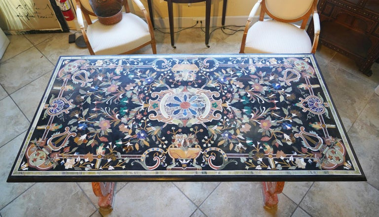Measuring 36 x 72 inches and dating to the 20th century this grand Pietra Dura dining table features an elaborately inlaid stone top with flowers, classical themes and cartouches in a multitude of colors. The table top rests on twin carved and