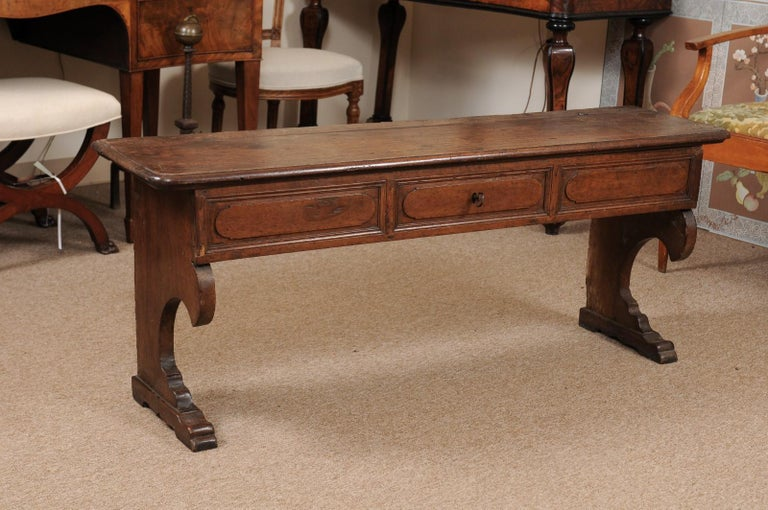 The Italian baroque walnut hall bench featuring lift top with enclosed interior and carved frieze supported by two carved C-scroll shaped legs.