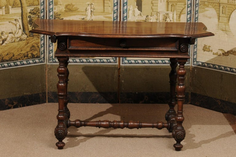 The late 17th century Italian Baroque console table in walnut with serpentine top, drawer below with wood pull and turned legs joined by stretcher ending turned feet.