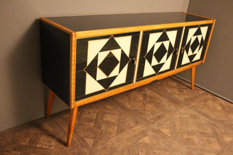 Very refined, this elegant sideboard features an eye-catching geometrical decor made of Murano glass plaques and brass inlay. The pompom shape brass handles on the doors add an elegant touch to this piece which is best showcased in an entryway, a