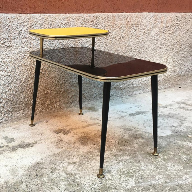Italian black and yellow Formica, wood and brass coffee table, 1960s. Italian coffee table with double shelf in polished black and matt yellow Formica. Wood legs and brass details, 1960s.