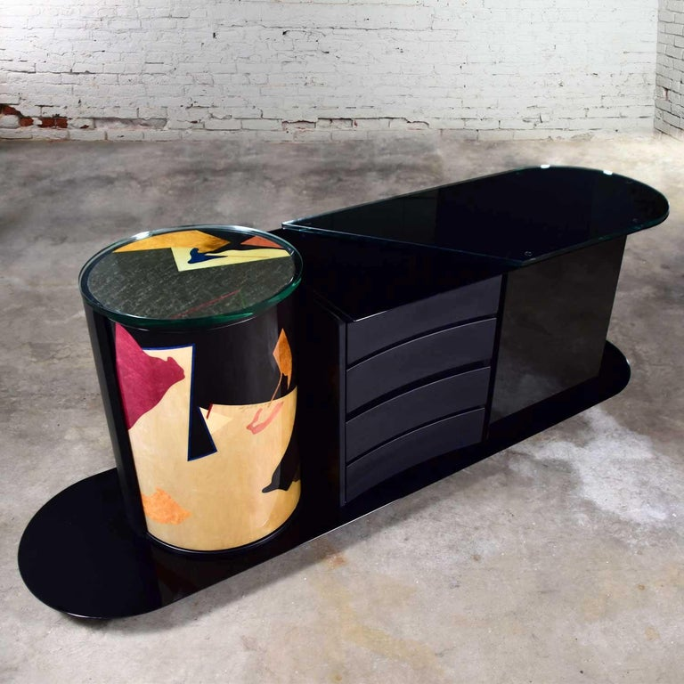 Stunning postmodern Italian black lacquered buffet, credenza, or sideboard signed by Pietro Costantini. Comprised of a highly lacquered black finish, cylinder shaped unit on one side with abstract geometrical designs in gold, green, red, blue, and