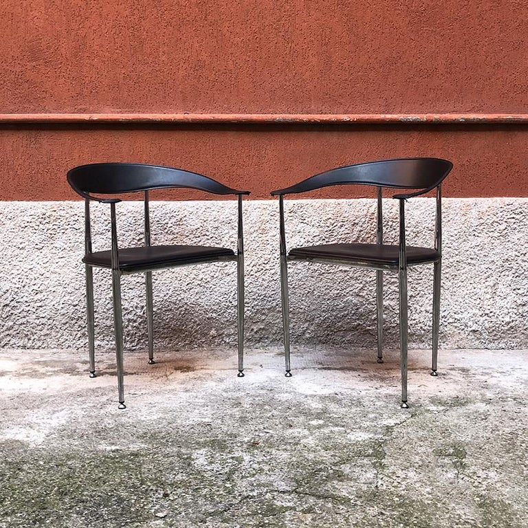 Italian black leather and chromed steel chairs, 1970s. Set of 2 beautiful Italian dining chairs, with armrests, seat and back in black leather and chromed steel structure. Very good general conditions.