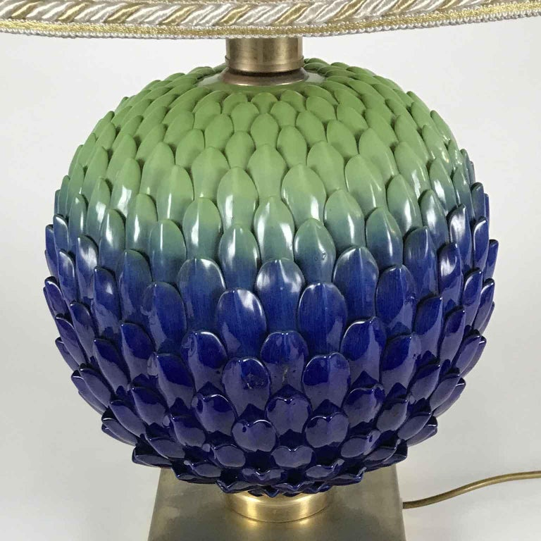 A Mangani porcelain circular table lamp from Italy, Florence. A unique design strobilus shaped, a pine cone or a strobiloid flower hand painted with polychrome decoration, blue and mint green petals of a circular bud flower or inflorescentes set on