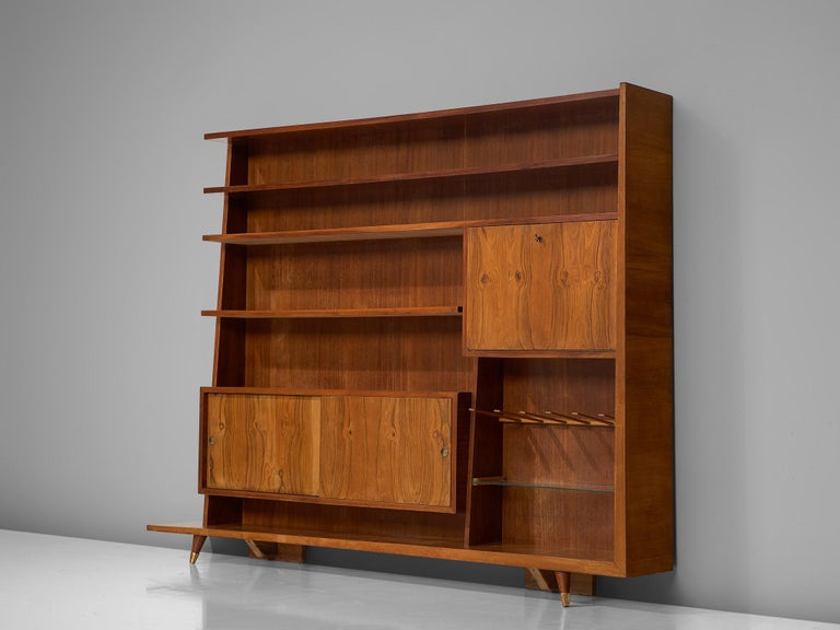 Bookcase, oak, walnut, brass and glass, Italy, circa 1950.  This sophisticated, large bookcase designed in Italy comes in a great size. With a nice variety of storage compartment and shelves, this pieces offers plenty of storage space and options