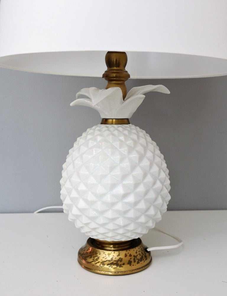 Gorgeous ceramic table lamp made of a white ceramic pineapple standing on a brass base and with brass details at the upper part.