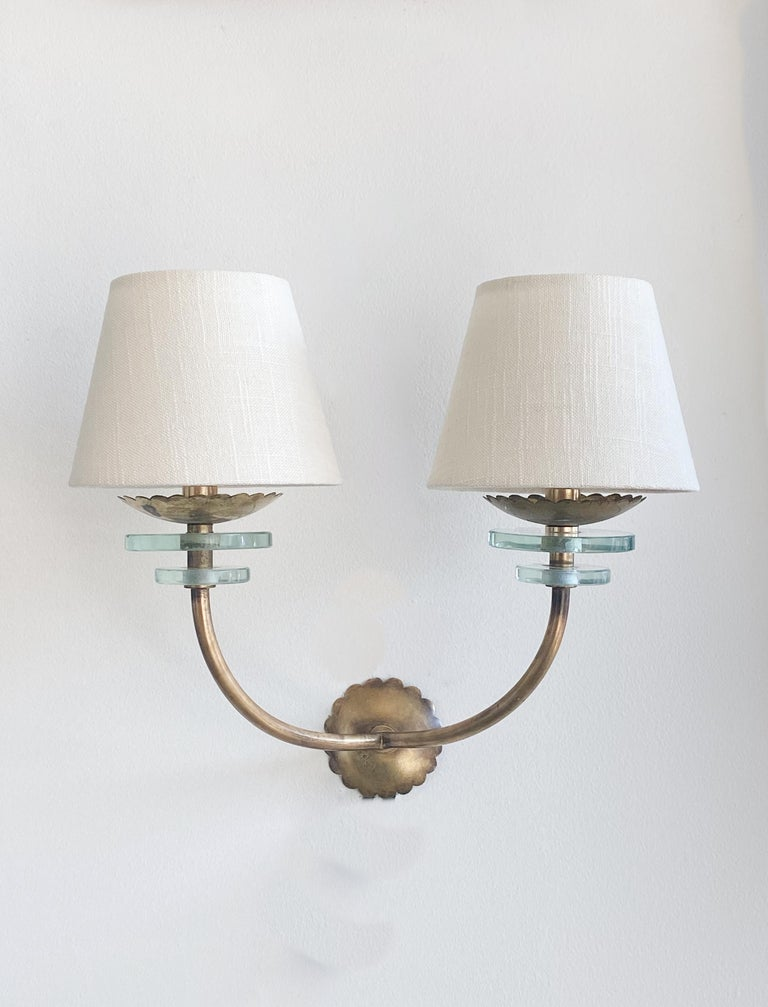 Pair of Italian 1950s brass and glass sconces. Each sconce has two curved brass arms with two glass discs on each arm and a scalloped brass backplate. Newly re-wired and new linen shades.