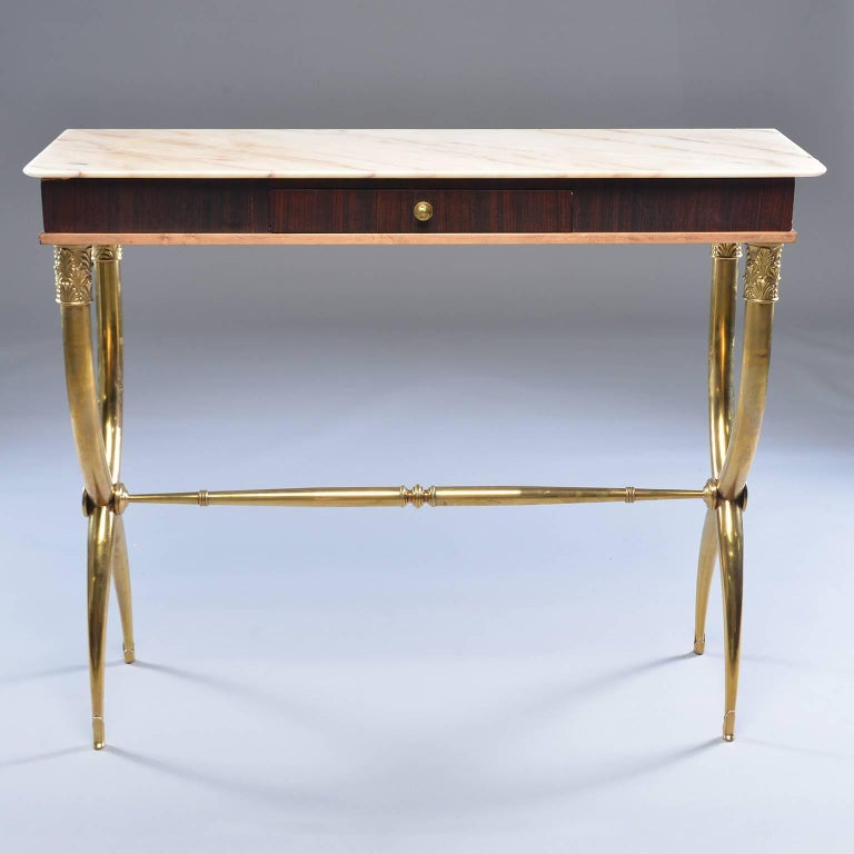 Italian neoclassical style console has brass base with X-form tapered legs embellished with acanthus leaf detail at top, tapered stretcher, wood table with single centre drawer and creamy marble top with pale apricot veins and streaks, circa 1960s.