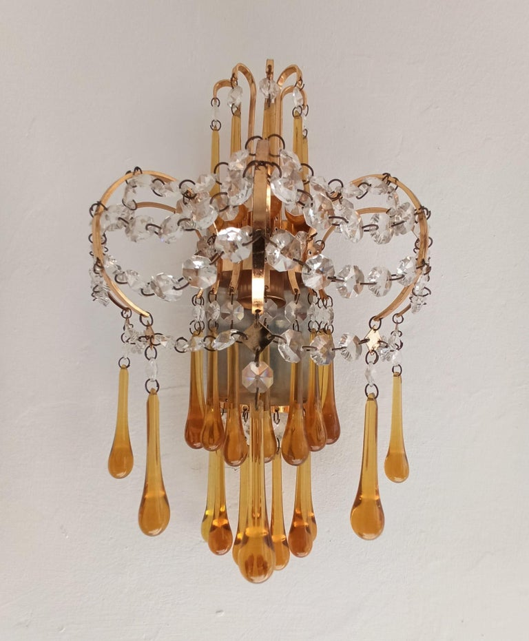 A beautiful original vintage Italian pair of wall lamps designed by Paolo Venini in the 1960s in brass and Murano glass surmounted at the top by a half moon crown of curved brass rods with amber glass drops suspended at the ends. The structure is