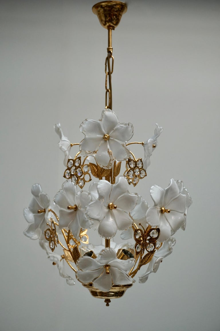 Italian brass chandelier with Murano glass flowers and crystal and brass butterfly. The light requires four single E14 screw fit lightbulbs (60Watt max.) LED compatible. Diameter 40 cm. Height fixture 44 cm. Total height with chain 75 cm.