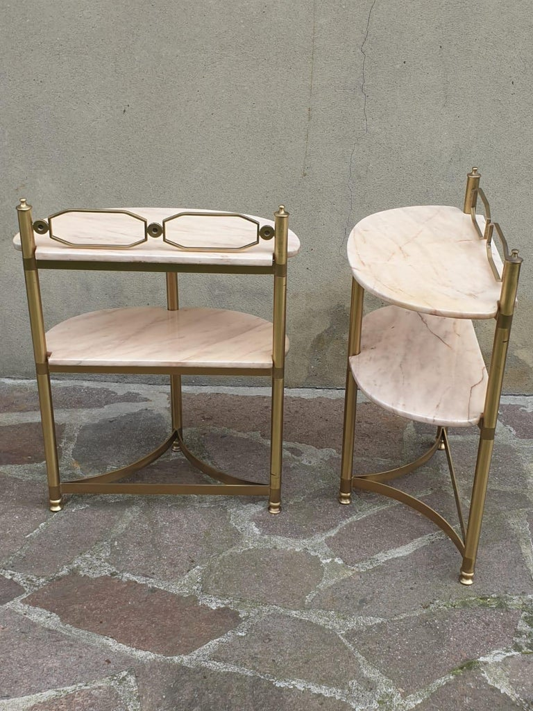 Pair of demi-lune side tables or night stands. Made in brass and Portuguese pink marble. Side tables are from the 1950 s period  It might show slight traces of use since it's vintage, but it can be considered as in excellent original condition and