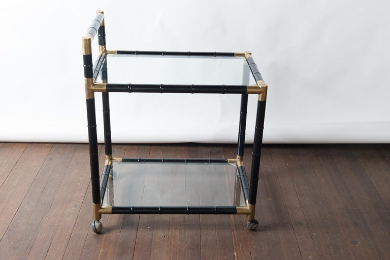 Black painted, brass trimmed, wood faux bamboo bar or drinks cart on ball casters.