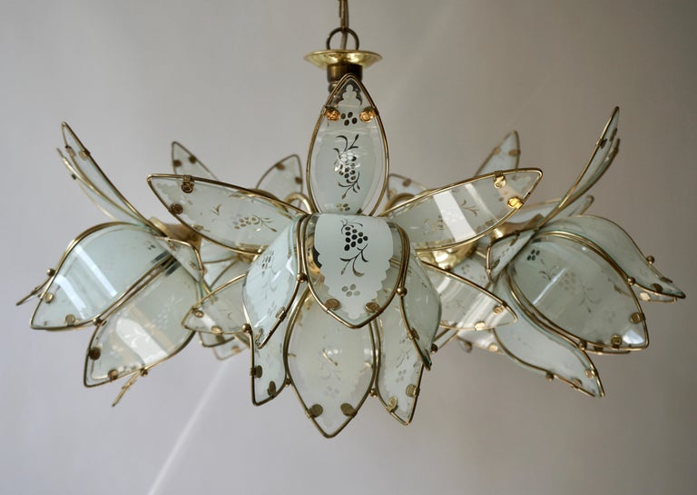 Italian chandelier in brass with five white Murano glass flowers.  Measures: Diameter 26.7 inch - 68 cm. Height fixture 15.7 inch - 40 cm. Total height including the chain and canopy is 35.4 inch - 100 cm.