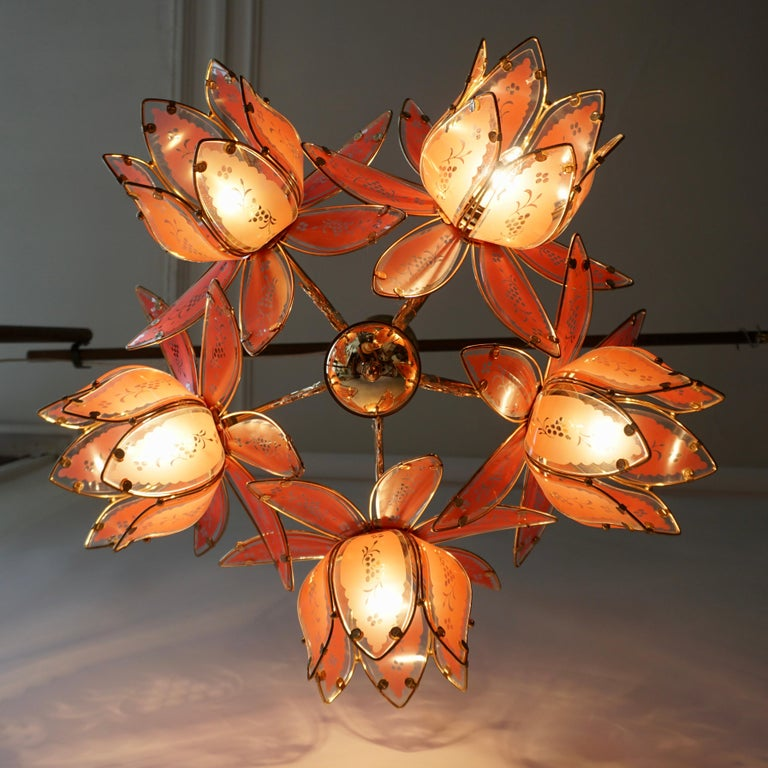 Italian chandelier in brass with five Murano glass flowers.The light created by this chandelier is very pleasant and ambient The light requires five single E27 screw fit lightbulbs (60Watt max.) LED compatible.  Measures: Diameter 26.7 inch, 68