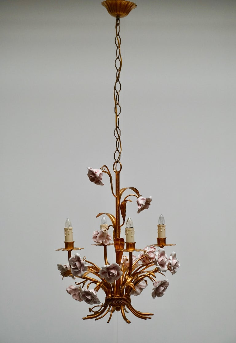 Italian Hollywood Regency brass gilt chandelier with pink porcelain flowers. Measures: Diameter 40 cm. Height fixture 52 cm. The total height including the chain and canopy is 100 cm.