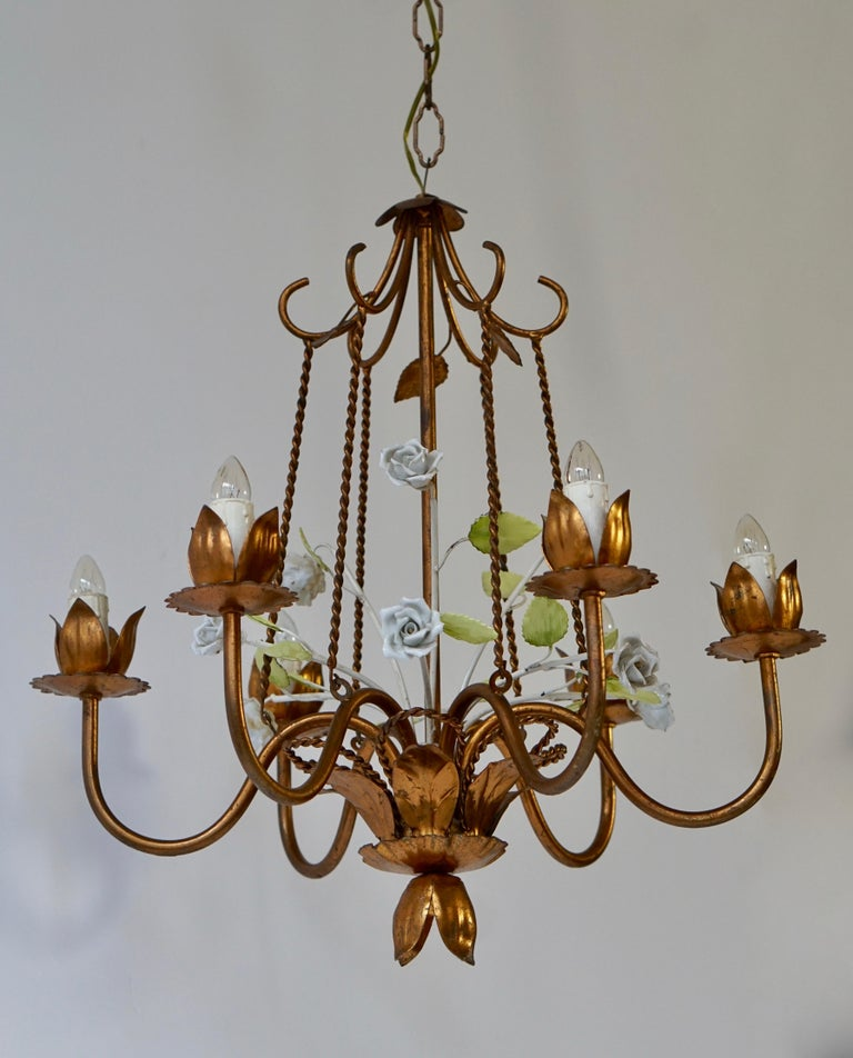 Brass chandelier with porcelain flowers and green leaves. Total height with the chain is 100 cm. Diameter 50 cm. Height fixture 52 cm. Six E14 bulbs.
