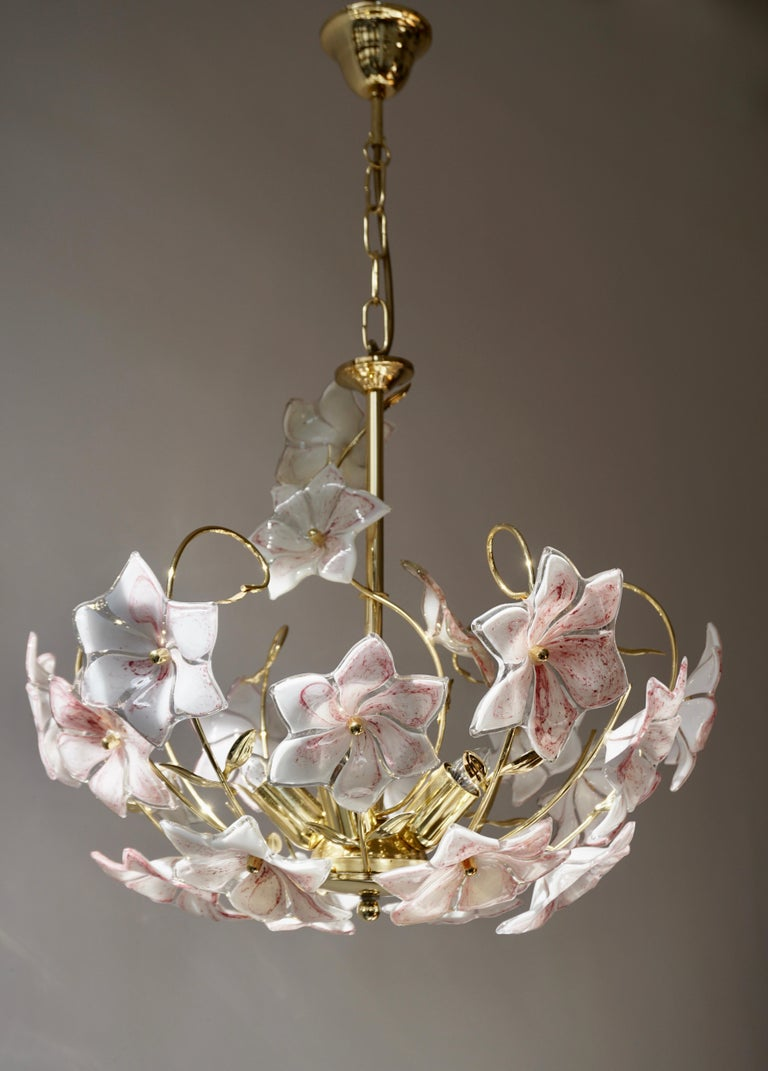 Italian brass chandelier whit white pink Murano colored glass flowers.  The light requires five single E14 screw fit lightbulbs (40Watt max.) Diameter 50 cm. Height fixture 44 cm. The total height is 65 cm with the chain. (Can be shortened).
