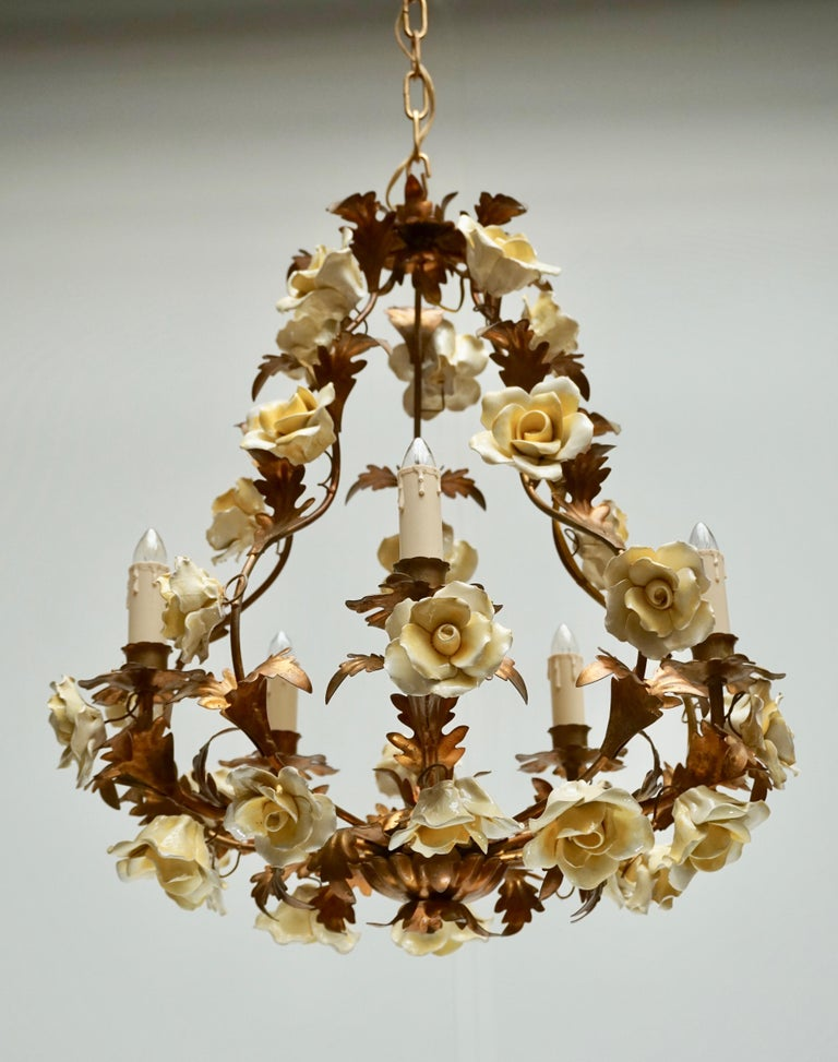 Italian Hollywood Regency six light chandelier in brass with yellow porcelain flowers. Diameter 50 cm. Height fixture 55 cm. Total height including the chain 180 cm.