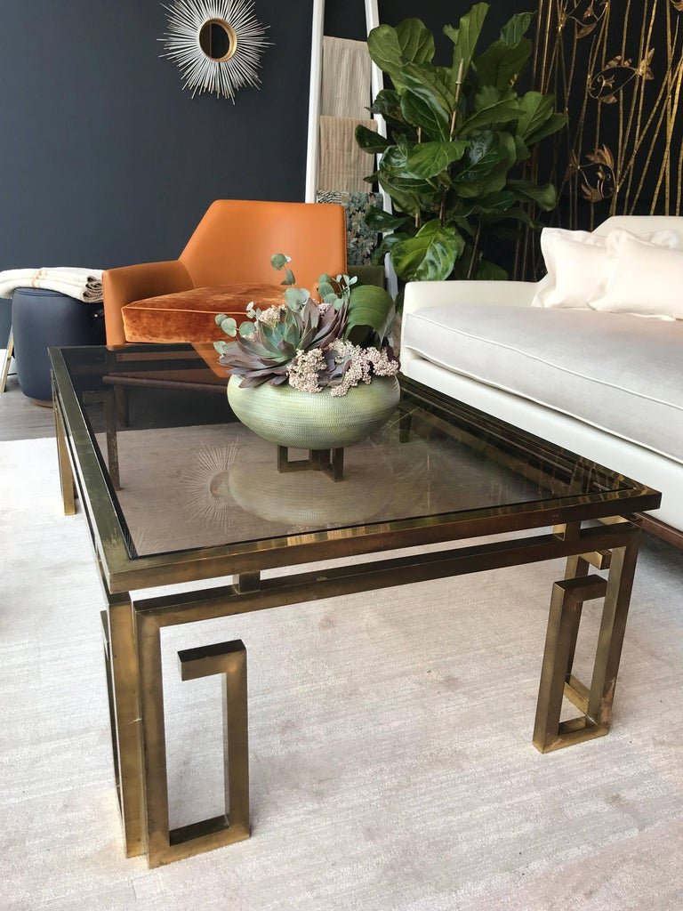 An Italian brass coffee table with ornate Greek key legs and smoked glass top.