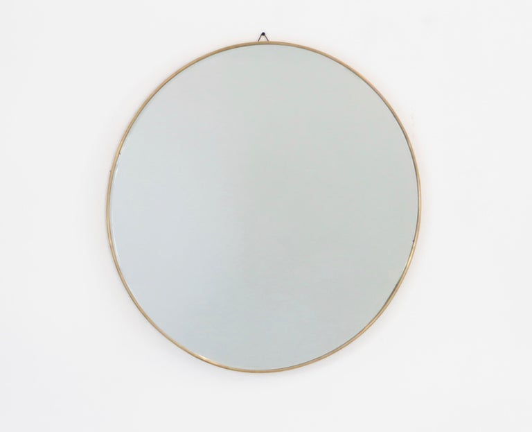 A round Italian vintage brass framed mirror with beautiful patina and no flaws to the original mirror, circa 1950.  The mirror has a .25
