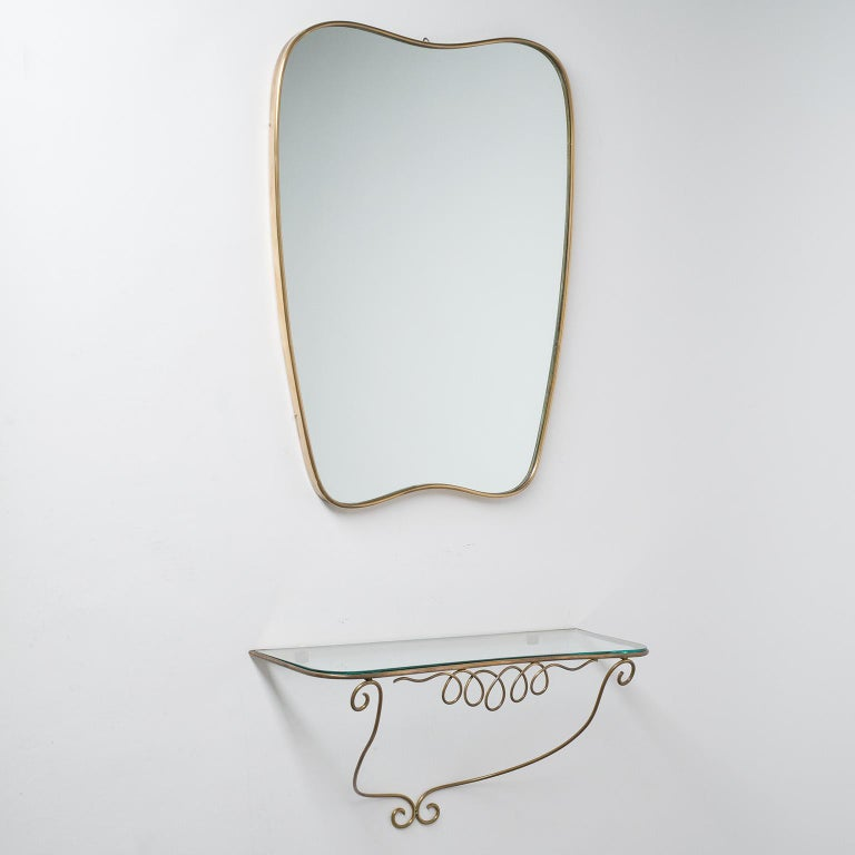 Italian brass mirror and console in the style of Gio Ponti, circa 1950.  Measures: Mirror height 59cm, width 45cm, depth 2.5cm; Console height 27cm, width 51cm, depth 18cm.