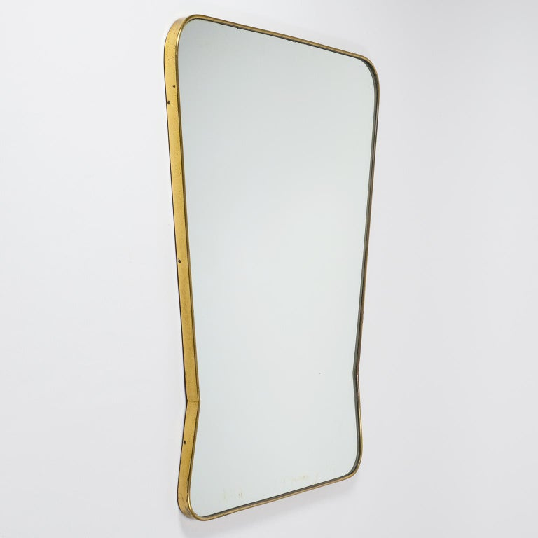 Very fine 1940s-1950s Italian brass mirror, attributed to Fonatan Arte. The continuous brass frame has a very unique tapered shape reminiscent of Gio Ponti designs. Good original condition with patina on the brass and some wear to the silver coating