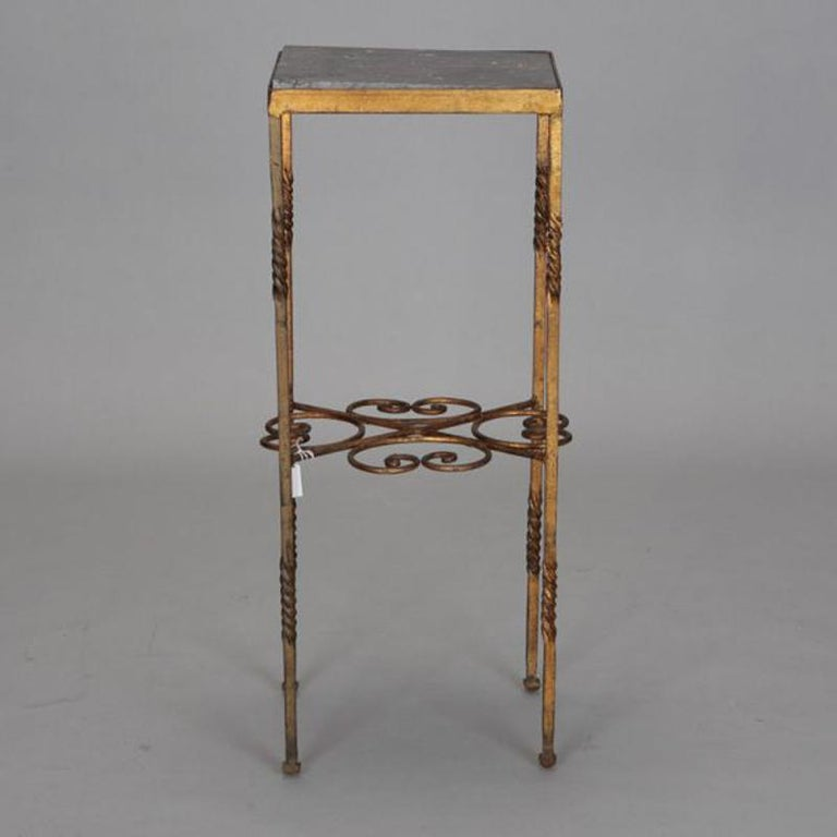 Italian statue stand has gilded wrought iron frame with dark marble tabletop, circa 1920s. Unknown maker.