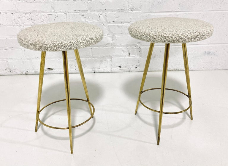 Chic low brass stools with cream boucle upholstery, Italian, circa 1950.