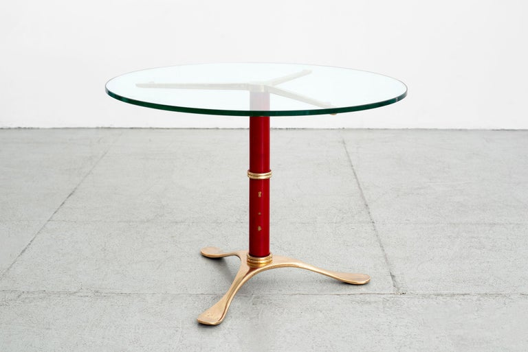 Solid brass tripod table in red enamel, glass top and sculpted brass base.