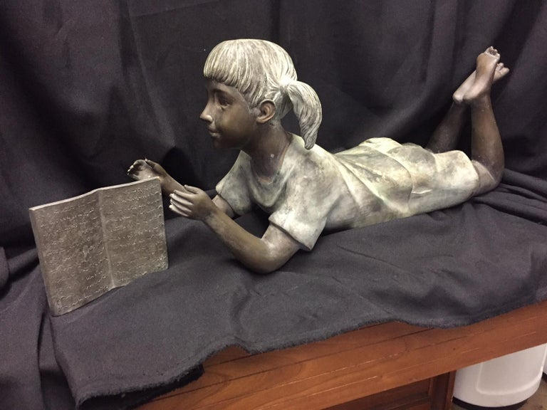 Cute Italian bronze figure of a pigtailed little girl laying on her belly with her legs crossed enjoying a book. Weathered patina. 