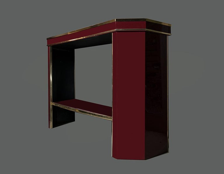 Italian Burgundy lacquered and brass console table with, brass edges, glass cover top.