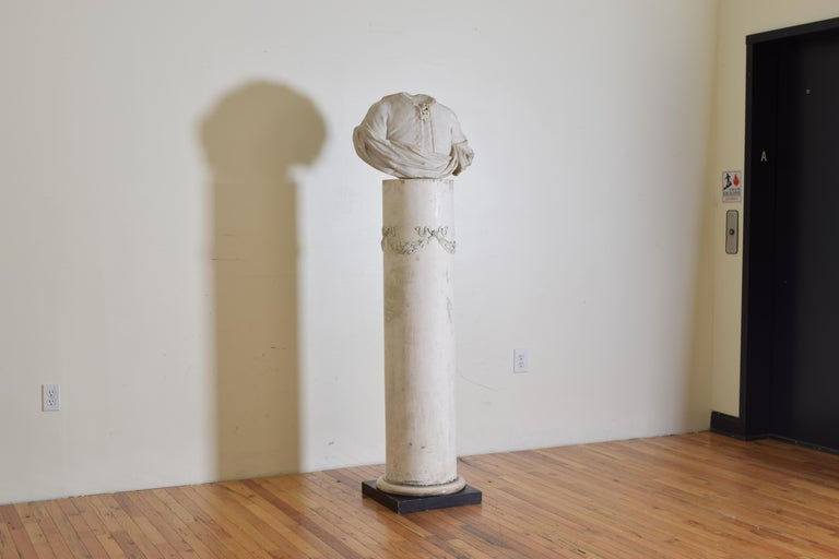 This headless bust in white marble adorned in 18th century clothing on a later plaster pedestal on square wooden base   Dimensions of bust: Length 21
