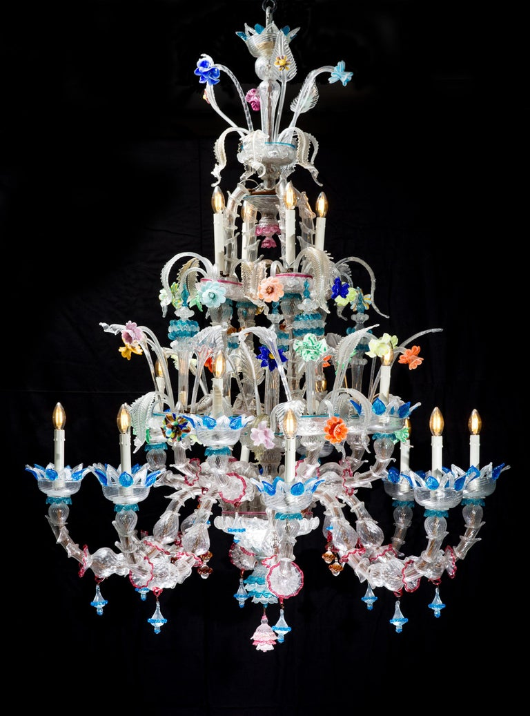 A very big colored Murano chandelier from Venetia in Italy. The chandelier was made in the mid-century period. The chandelier has a total of 16 arms. 12 of the 16 arms have a light bulb and the remaining 4 arms have an ornated peak. At the top of