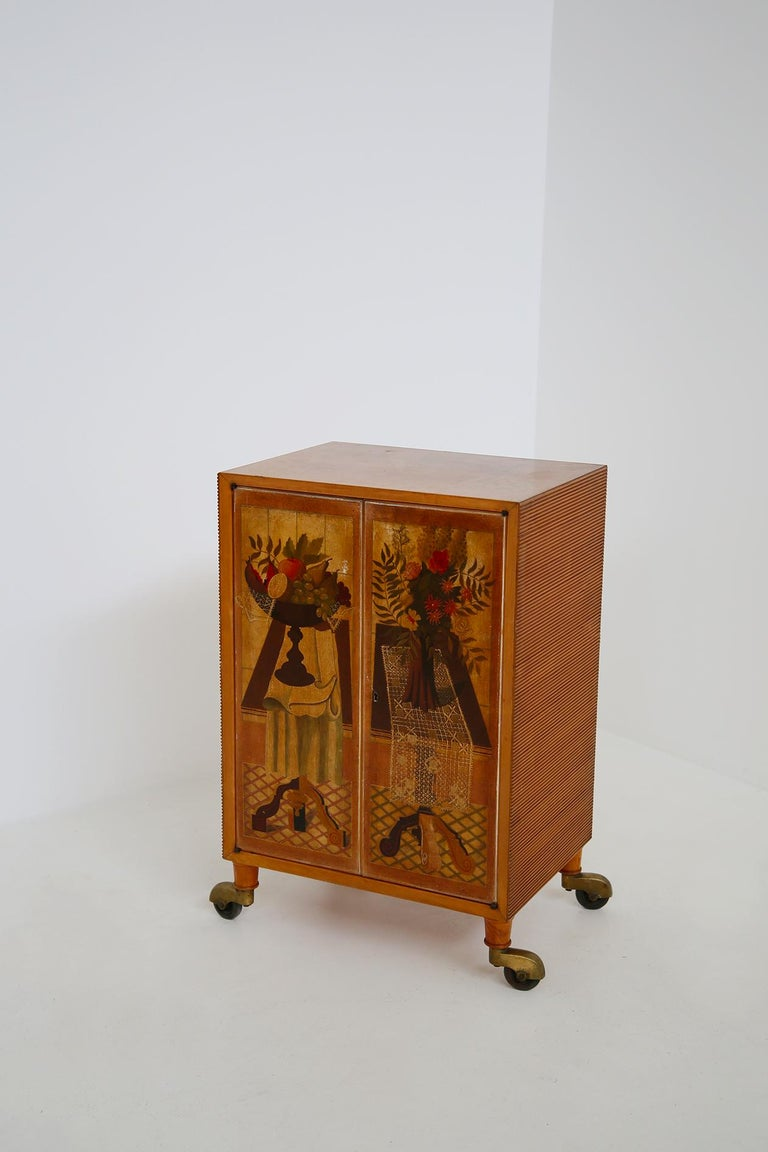 Scremin Luigi. Elegant and well represented cabinet designed by Marino Meo's preparatory cardboard. The production is by the Scremin Brothers, Belluno 1940s. With original label. The feet are made on wheels with brass wheel covers. The cabinet is