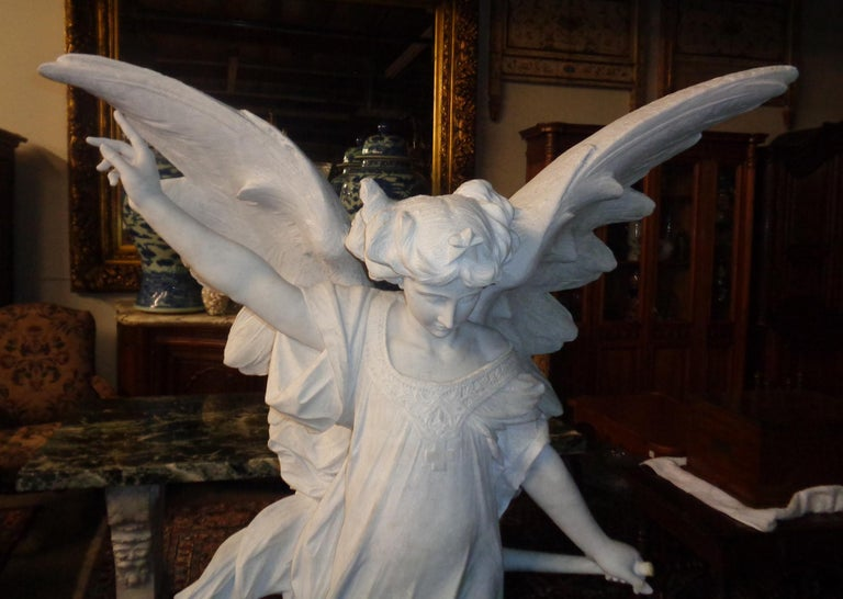 Magnificent life-size Italian Carrara marble sculpture of a winged angel standing on a cloud atop a rectangular base. The right hand is pointing to the heavens and the left hand is holding a trumpet. The angel is carved from a single block of