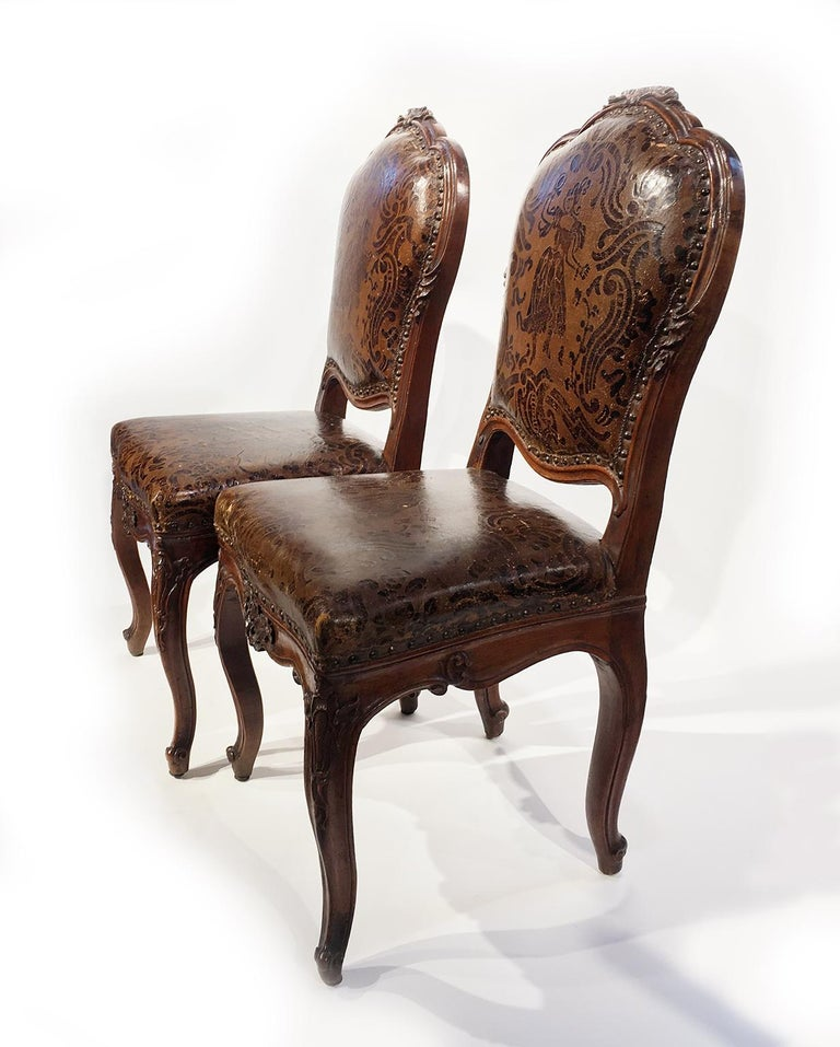Four carved walnut chairs with leather covers