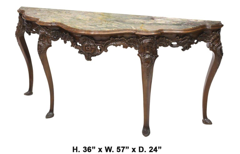 Uniquely shaped 19th century Italian carved walnut long console  The beautiful exotic serpentine-fronted inset marble top is over Rocaille motif frieze finely carved with foliate C-scrolls, supported by four cabriole legs terminating in carved feet.