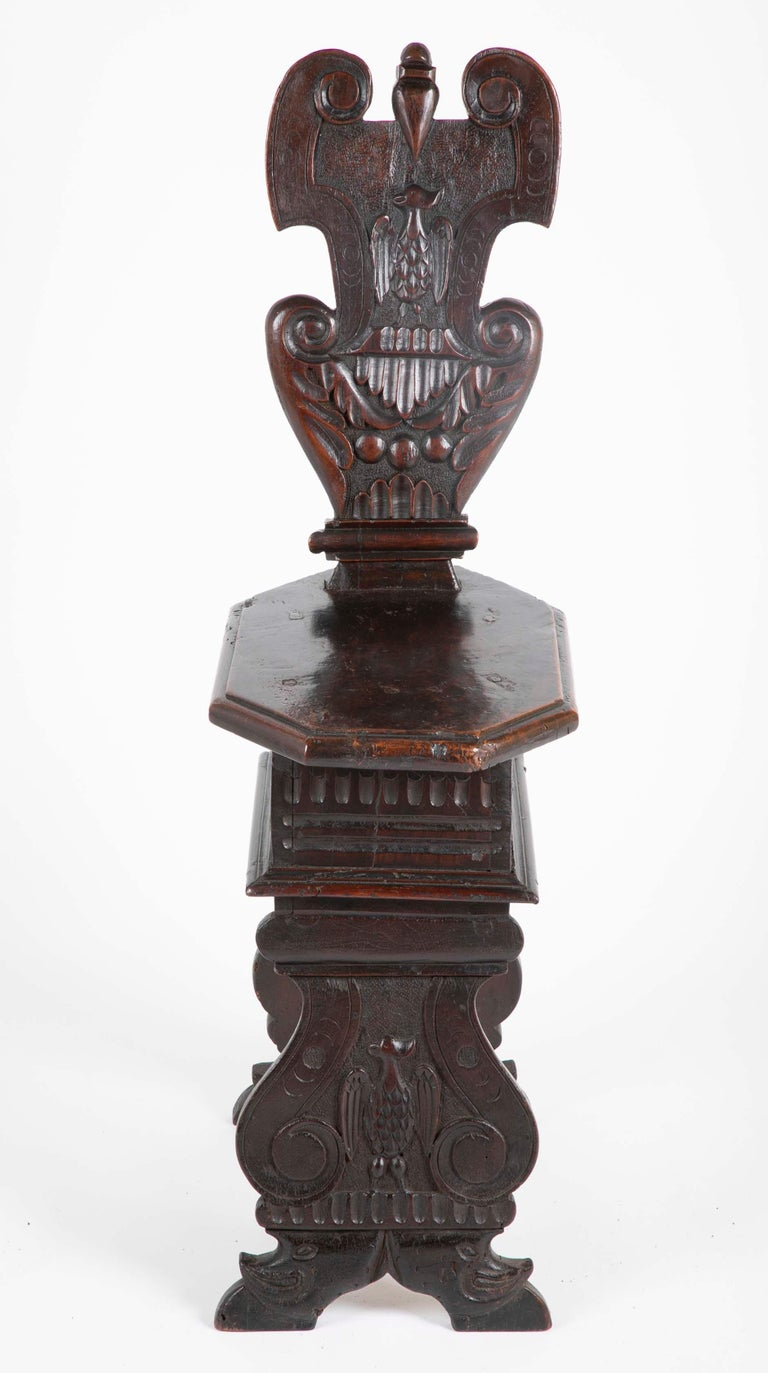 A late 16th, early 17th century walnut sgabello, or hall chair with a cartouche shaped back carved with an eagle in relief. The octagonal seat above scrolled supports, also carved with the image of an eagle. This is the classic late Renaissance,