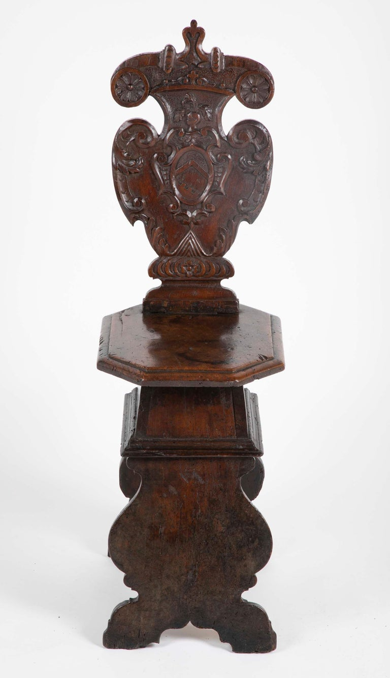 A late 16th, early 17th century walnut sgabello, or hall chair with a cartouche shaped back carved with a coats of arms armorial. The octagonal seat above scrolled supports. This is the classic late Renaissance, early Baroque form of a hall or
